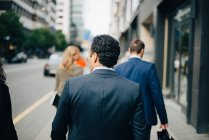 Rear view of businessman walking behind colleagues on sidewalk in city — Stock Photo