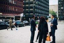 Colleghi uomini e donne in piedi sul marciapiede contro gli edifici in città — Foto stock