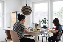 Мати і дочка, маючи продовольства в обідній стіл — стокове фото
