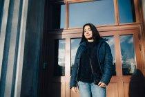 Retrato de bajo ángulo de adolescente confiada de pie contra la puerta de entrada en la ciudad - foto de stock