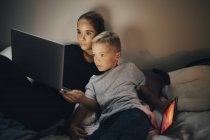 Ragazzo con tablet digitale sdraiato sul letto da sorella utilizzando il computer portatile a casa — Foto stock