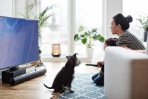 Mother and daughter watching television while sitting with dog on floor at home — Stock Photo