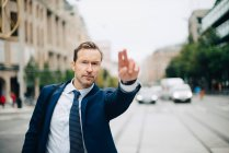 Portrait of confident mature businessman hailing taxi on street in city — Stock Photo