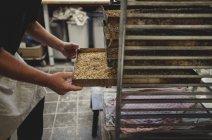 Mittelteil des Bäckers halten gebackenes Brot im Tray auf Kühlregal in Bäckerei — Stockfoto