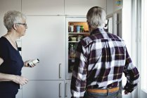 Senior couple standing by refrigerator in kitchen at home — Stock Photo