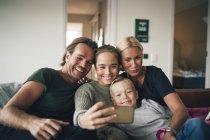 Famiglia sorridente scattare selfie attraverso lo smartphone mentre si siede sul divano a casa — Foto stock