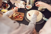 Cropped image of siblings decorating cake at kitchen counter — Stock Photo