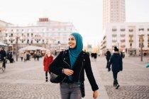 Sorridente giovane donna musulmana che indossa hijab a piedi sul sentiero in città — Foto stock