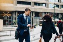 Uomo d'affari che utilizza smart phone mentre cammina da donna sul sentiero in città — Foto stock