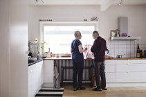 Full length rear view of retired senior couple standing in kitchen at home — Stock Photo