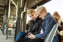 Menino adolescente mostrando telefone celular para menina adolescente enquanto sentado na plataforma da estação ferroviária — Fotografia de Stock