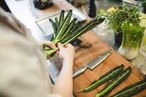 Torso de mujer chef preparar vegetales en la cocina - foto de stock