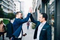Colegas de negócios macho maduro feliz dando toca aqui em pé na calçada na cidade — Fotografia de Stock
