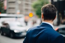 Rear view of mature businessman looking away while standing in city — Stock Photo