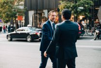 Mature businessman greeting male colleague on street in city — Stock Photo