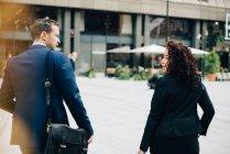 Задній вид багатоетнічного бізнес колег ходіння по стежка у місто — стокове фото