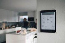 Aplicación de termostato en la tableta digital montada sobre la pared blanca en casa - foto de stock