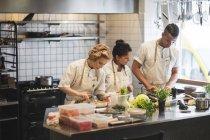 Chefs multiétnicos preparando comida en el mostrador de la cocina en el restaurante - foto de stock