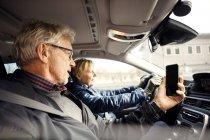 Uomo in possesso di smart phone mentre seduto da donna anziana guida auto in città — Foto stock