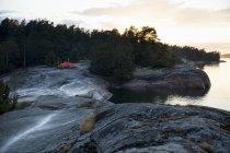 Vue éloignée de tente sur les rochers de lac dans le ciel au coucher du soleil — Photo de stock
