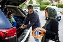 Мати тримає трубу в той час як батько підтримання електричного зарядного сина в машині — стокове фото