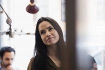 Улыбающаяся бизнесвумен, отворачивающаяся в творческом офисе — стоковое фото