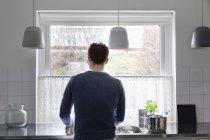 Vue arrière de l'homme travaillant dans la cuisine à la maison — Photo de stock