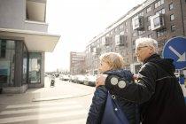 Vue arrière du couple de personnes âgées marchant sur la rue de la ville contre un ciel dégagé — Photo de stock