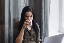 Blogger bebiendo café mientras trabaja en una oficina creativa - foto de stock