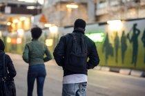 Vue arrière d'amis marchant sur une rue éclairée — Photo de stock