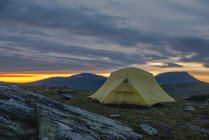 Yellow tent on mountain plain against cloudy sky during sunset — Stock Photo