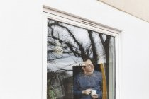 Homem que prende o copo de café que olha através do indicador ao estar na casa — Fotografia de Stock