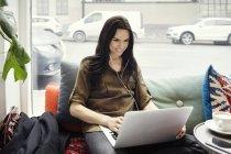 Улыбающаяся деловая женщина с ноутбуком, сидя на диване у окна — стоковое фото