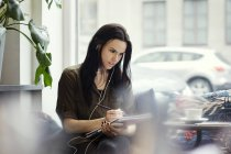 Kreative Geschäftsfrau trägt Kopfhörer beim Schreiben in Spiral-Notebook im Büro — Stockfoto