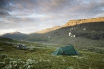 Tenda na encosta da montanha contra céu nublado — Fotografia de Stock