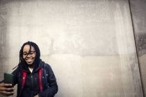 Opinião de baixo ângulo do adolescente de sorriso que toma o selfie através do telefone esperto de encontro à parede — Fotografia de Stock