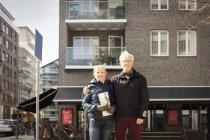 Ritratto di sorridente coppia anziana in piedi contro edificio — Foto stock