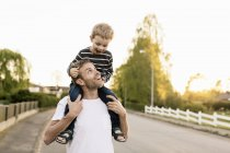 Happy father carrying son on shoulders while standing at street against clear sky — Stock Photo