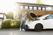 Padre hablando por teléfono de pie con el niño por el coche roto en la calle - foto de stock