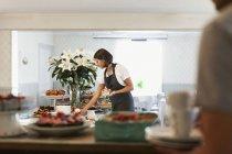 Пекарь накрывает на стол десерты, пока коллега-мужчина стоит в кафе — стоковое фото