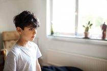 Nachdenklicher Junge steht zu Hause am Fenster — Stockfoto