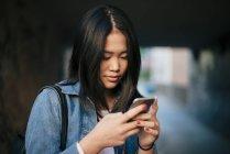 Adolescente, usando el teléfono inteligente en la ciudad de - foto de stock