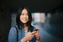 Portrait d'adolescente souriante tenant un téléphone intelligent en ville — Photo de stock