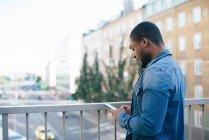 Vista laterale del giovane che usa lo smartphone mentre è in piedi sul ponte pedonale in città — Foto stock