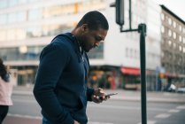 Vista lateral del joven usando un teléfono inteligente mientras está parado contra el edificio en la ciudad - foto de stock