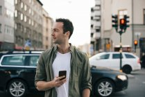 Uomo guardando lontano mentre tiene lo smart phone in città — Foto stock