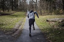 Full length rear view of determined male athlete jogging on narrow street in forest — Stock Photo