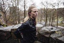 Вид збоку вдумливі спортсменка, стоячи на скелі в лісі — стокове фото