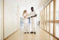 Повна довжина жіночого та чоловічого медсестер, обговорюючи над документа в лікарні коридор — стокове фото