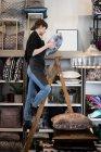 Jungunternehmerin steht auf Leiter und arrangiert Kissen im Regal im Geschäft — Stockfoto